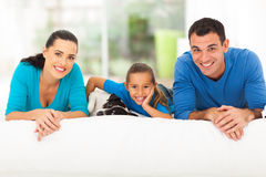 Family lying on bed. Happy young family lying on bed with their pet dog at home Stock Photos