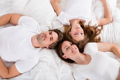Family Lying On Bed. High Angle View Of A Happy Family Lying On Bed Royalty Free Stock Photography