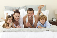 Family lying in bed with pyjamas. Happy young family lying in bed with pyjamas Royalty Free Stock Image