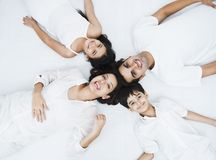 Family lying on a bed. And smiling Stock Photo
