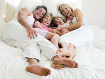 Family lying in bed smiling Stock Image