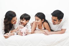 Family lying on a bed. Smiling family lying on a bed with women putting coin in a piggy bank Royalty Free Stock Photos