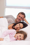Family lying on the bed together. Young family lying on the bed together Royalty Free Stock Photos