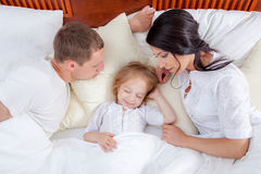 Family lying on a bed together in bedroom Stock Photography