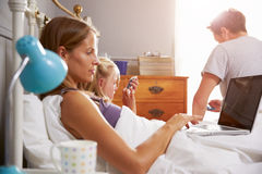 Family Lying In Bed Together Using Digital Devices Stock Photo