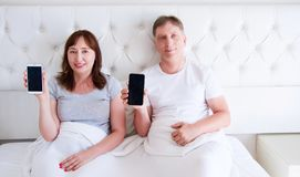 Family lying in the bedroom and holding mobile phones. Middle aged family stock image