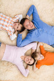 Family  lying on the carpet Royalty Free Stock Image