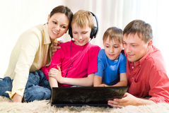 Family lying on the carpet with a laptop Royalty Free Stock Photos