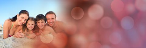 Family lying down at beach with red bokeh transition Stock Photos