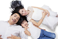 Family lying down on the floor in studio Stock Photography