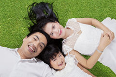 Family lying down on green grass Royalty Free Stock Photography