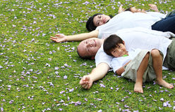Family lying down in the park Stock Photos