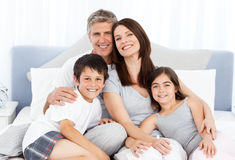 Family  lying down on their bed Royalty Free Stock Image