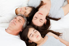 Family  lying down on their bed Stock Photography