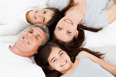 Family lying down on their bed Stock Images