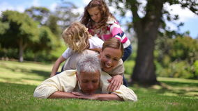 Family lying on a fathers back Royalty Free Stock Images