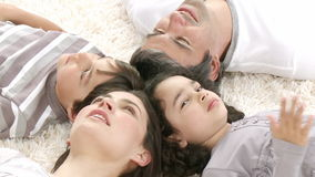 Family lying on floor with heads together Stock Photos