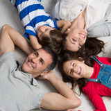 Family Lying On Floor. High Angle View Of Happy Family With Two Children Lying On Floor Royalty Free Stock Photos