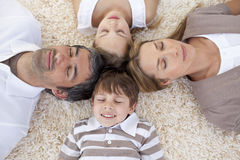 Family lying on floor at home with heads together Stock Images