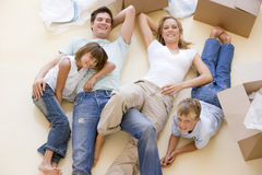 Family lying on floor by open boxes in new home. Smiling Royalty Free Stock Photos
