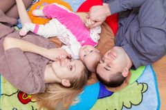 Family are lying on the floor with their baby Royalty Free Stock Image