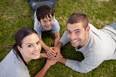 Family lying on garden with hands together. Happy parents and kid lying on garden with hands together Stock Image
