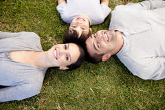 Family lying on garden with heads together Stock Photos