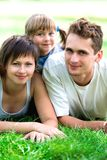 Family lying on grass. Young Family Lying on the Grass in Park Stock Photos