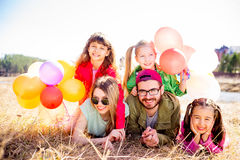 Family lying on grass with balloons Stock Photography
