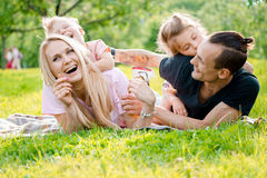 Family lying on grass in countryside. Young big happy family lying on grass in countryside Royalty Free Stock Photography