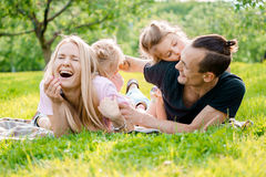 Family lying on grass in countryside. Young big happy family lying on grass in countryside Stock Photo