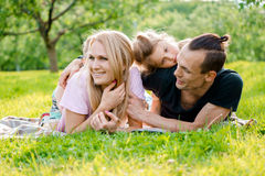 Family lying on grass in countryside. Young big happy family lying on grass in countryside Stock Image