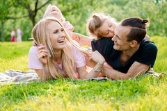 Family lying on grass in countryside. Young big happy family lying on grass in countryside Stock Photos
