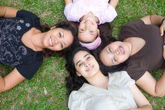 Family lying on grass in outdoor park Stock Image