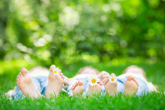 Family lying on grass. Outdoors in spring park Royalty Free Stock Image
