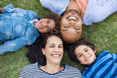 Family lying on grass. Overhead view of cheerful family lying on grass in a circle and looking at camera. High view of multiethnic family lying on grass at park royalty free stock photos