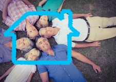 Family lying on grass overlaid with house shape Stock Photo
