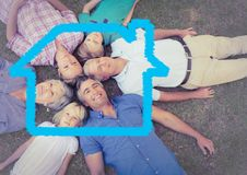 Family lying on grass overlaid with house shape Royalty Free Stock Photo