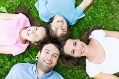 Family lying on grass. Portrait of a happy family outdoors stock images