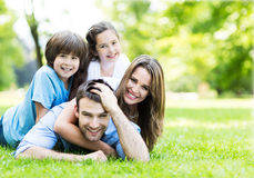 Family lying on grass. Portrait of a happy family outdoors Royalty Free Stock Photo