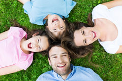 Family lying on grass. Portrait of a happy family outdoors royalty free stock image