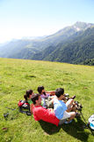 Family lying in grass relaxing in the mountains Stock Photos