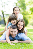 Family lying on grass smiling. Portrait of a happy family outdoors stock image