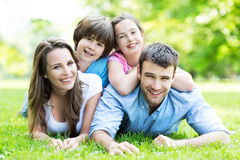 Family lying on grass smiling. Portrait of a happy family outdoors royalty free stock photography