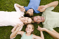 family lying on ground holding hands in a star shape Royalty Free Stock Photography
