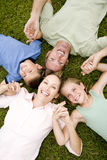 family lying on ground holding hands in a star shape Royalty Free Stock Image