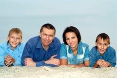Family  lying on light sand Royalty Free Stock Photo