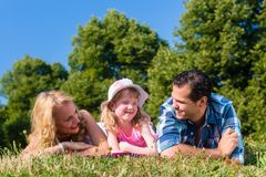 Father, mother, daughter lying on meadow in grass Stock Images