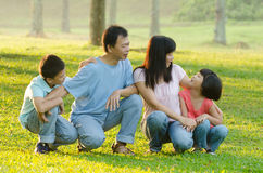 Family lying outdoors being playful and smiling Royalty Free Stock Photo