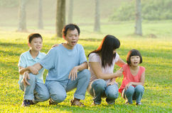 Family lying outdoors being playful and smiling Stock Image
